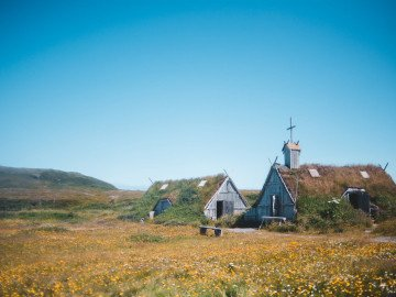 rustic timber house and church on blooming meadow in hilly countryside