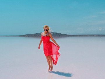 woman in sunglasses jumping over wet sand