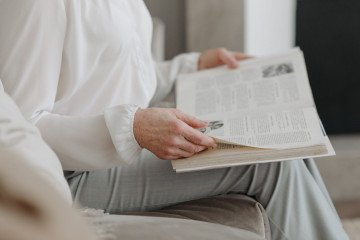 person in white long sleeves reading a book