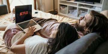 man and woman lying on bed using laptop computer